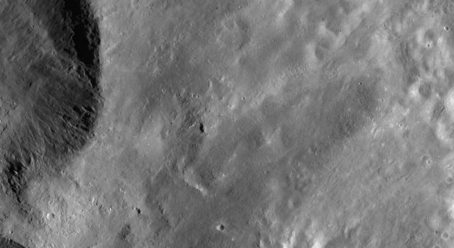 "This image from NASA's Dawn spacecraft shows ejecta from two of the large ""Snowman"" craters on the left of the image. This ejecta smooths out asteroid Vesta's surface in the rest of the image."