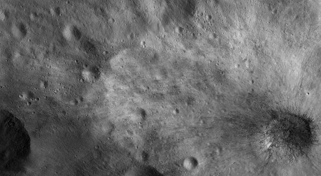 This image from NASA's Dawn spacecraft shows a young, fresh crater, which is about 7 km in diameter, on asteroid Vesta. This crater has both dark and bright rays fanning out from it.