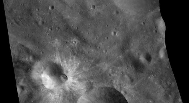 This mosaic of three images was taken by NASA's Dawn framing camera during the high-altitude mapping orbit over the giant asteroid Vesta. The eastern rim is higher than the western rim, and the overall topography is downhill from east to west.