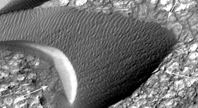 This image, from an animation from NASA's Mars Reconnaissance Orbiter shows a dark, rippled sand dune overlying bright-toned rock.