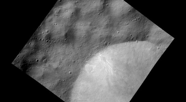 This image from NASA's Dawn spacecraft shows a relatively fresh crater with bright deposits exposed in the crater wall that streak downslope on the giant asteroid Vesta.