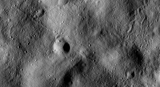 This image from NASA's Dawn spacecraft shows many linear or sinuous grooves crisscrossing the surface of asteroid Vesta. They were created when large pieces of debris grazed and scoured the surface.