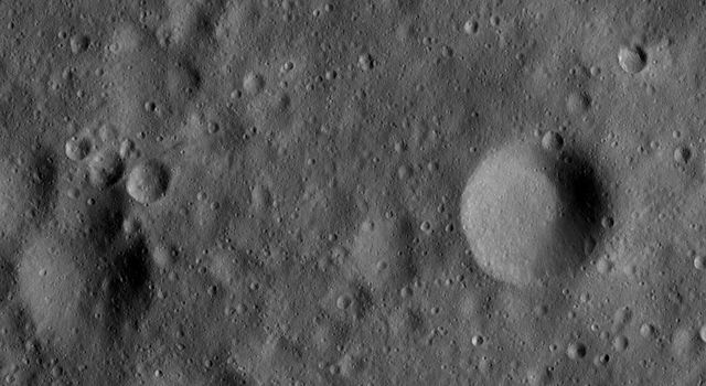This image from NASA's Dawn spacecraft shows a large number of craters, formed by collisions into the surface of asteroid Vesta. The relatively large circular depressions in this image are older, heavily degraded impact craters.