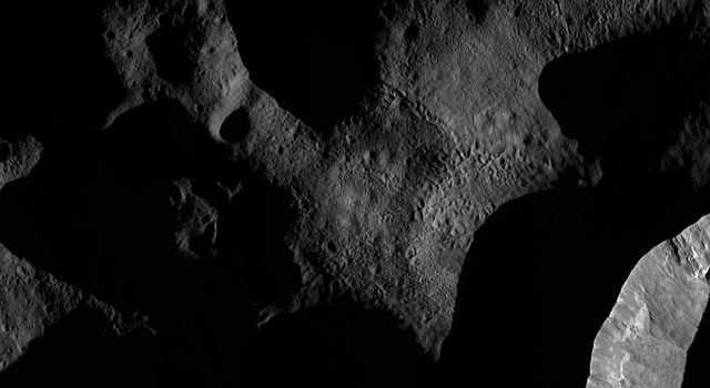 This image from NASA's Dawn spacecraft shows the sun illuminating the landscape of asteroid Vesta during a Vestan 'sunrise'; the sun had a low angle relative to Vesta's surface, just as the sun has a low angle in the sky in the morning on Earth.