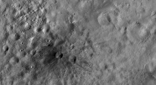 This image from NASA's Dawn spacecraft shows Aricia Tholus, a dark hill located in asteroid Vesta's Marcia quadrangle. Tholus is a word used to describe a small dome-like mountain or hill. Aricia was the name of a city in ancient Italy.