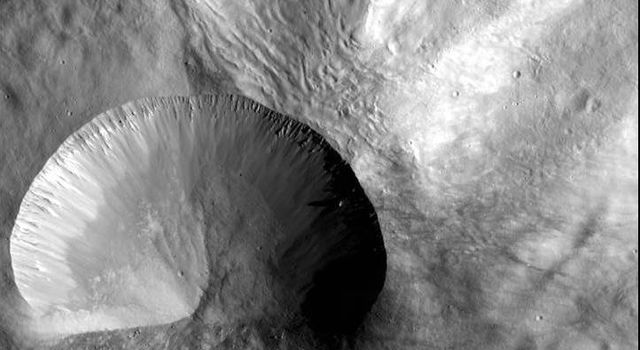 This image from NASA's Dawn spacecraft shows a young crater on asteroid Vesta. Layering is visible in the crater walls, as are large boulders that were thrown out in the material ejected from the impact.