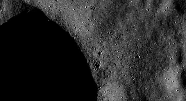 The low sun elevation in this image of NASA's Dawn spacecraft of asteroid Vesta enhances small topographic details near the rim of the large crater, part of which is visible in the bottom left of the image.