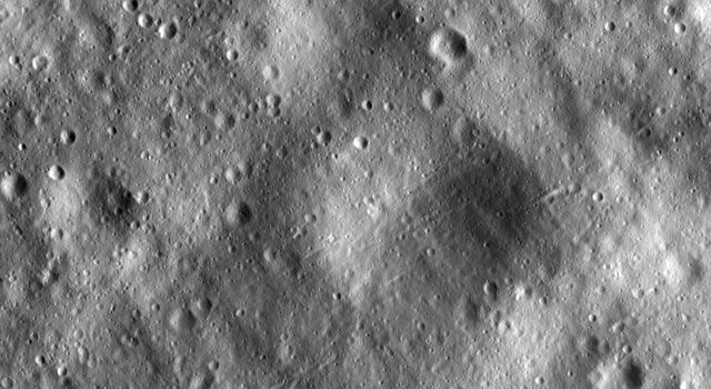 This image from NASA's Dawn spacecraft shows many large subdued craters that have smaller, younger craters on top of them on asteroid Vesta. There are two large subdued craters in the center of the image, which have very degraded and rounded rims.