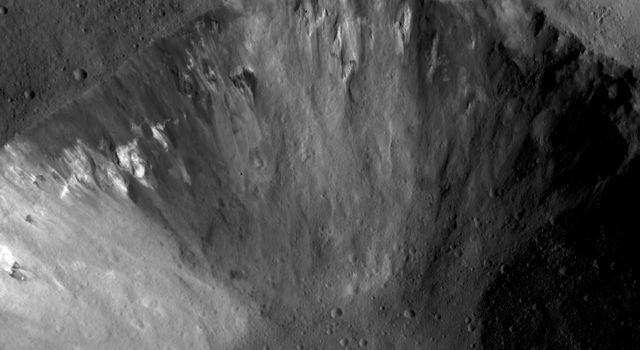 This image from NASA's Dawn spacecraft shows part of a large crater that has an irregularly shaped, fresh rim and is distinctive because it has many outcrops of dark and bright material originating from its rim and from the interior slope of the crater.