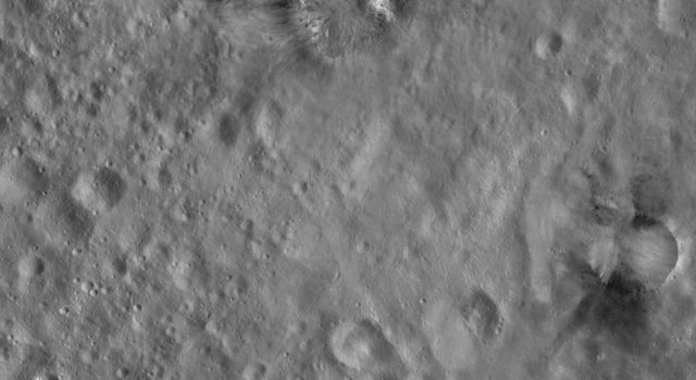 This image from NASA's Dawn spacecraft of asteroid Vesta shows Rubria and Occia craters. Both Rubria and Occia contain dark and bright material and both have reasonably sharp, well-defined and regularly shaped rims.