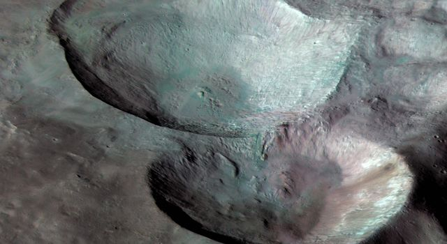 Three impact craters of different sizes, arranged in the shape of a snowman, make up one of the most striking features on Vesta, as seen in this view from NASA's Dawn mission.