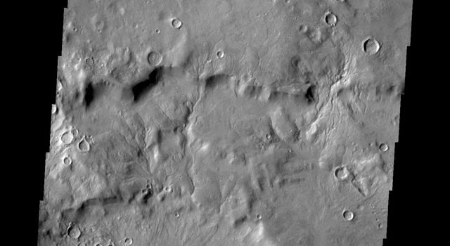 Small channels dissect the inner rim of this unnamed crater in Arabia Terra as seen by NASA's 2001 Mars Odyssey spacecraft.