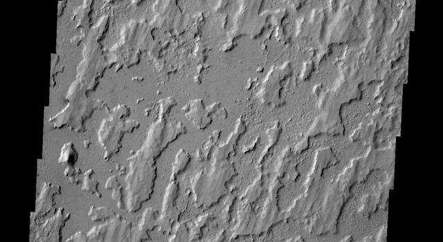 The unusual texture in this image from NASA's 2001 Mars Odyssey spacecraft is located on the plains of Elysium Planitia. The surface appears to be layered. The top layer has parallel, linear hills and channels.