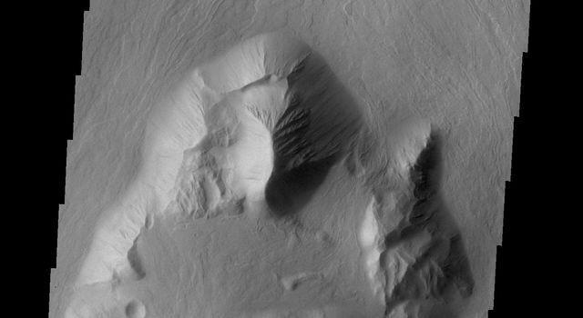 This image from NASA's 2001 Mars Odyssey spacecraft shows lava flows which have plunged over the steep escarpment marking the edge of Olympus Mons into the surrounding plains.