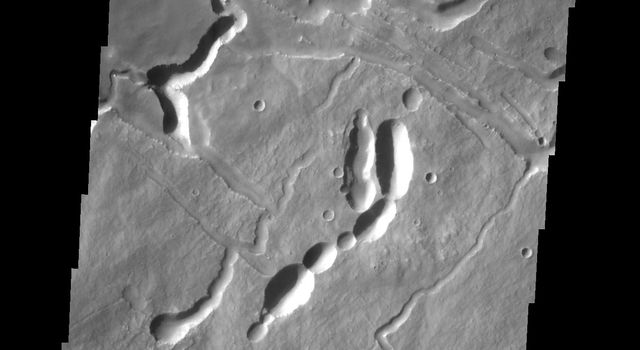 This image from NASA's 2001 Mars Odyssey spacecraft shows the complex surface on the northeastern flank of Arsia Mons. The channel-like features and collapse pits are likely all due to subsurface lava tubes.