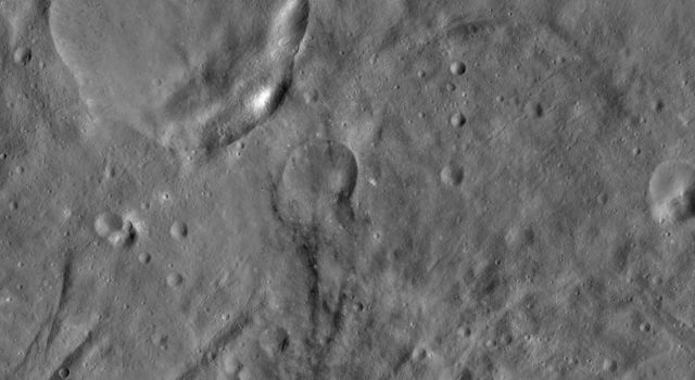 This image from NASA's Dawn spacecraft of asteroid Vesta shows Urbinia and Sossia craters, located in Vesta's Urbinia quadrangle. Urbinia is the large crater, and Sossia is the small crater surrounded by dark material in the bottom of the image.