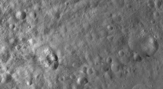 This image from NASA's Dawn spacecraft of asteroid Vesta shows Teia crater, which is the crater with bright and dark material. There is mostly bright material in Teia crater but there is also a patch of dark material on one side.