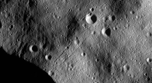 This image from NASA's Dawn spacecraft of asteroid Vesta shows chains of craters on an undulating surface probably formed of fine-grained debris, called regolith, which was ejected from large impact craters as they formed nearby.