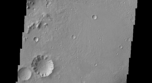 This image from NASA's 2001 Mars Odyssey spacecraft shows the northwestern floor and rim of Gale crater on Mars. A channel dissects the rim, and the edge of the central mound is visible in the bottom right corner.