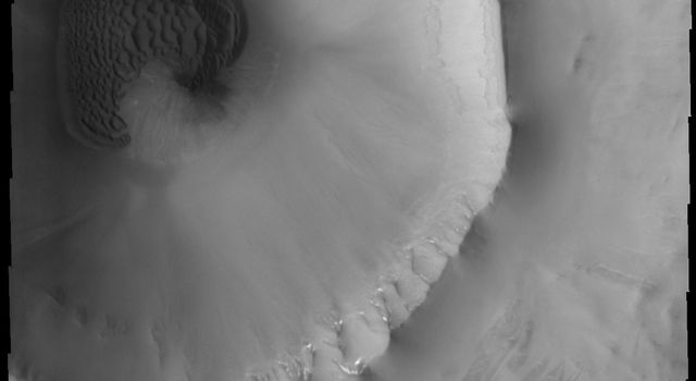 This image from NASA's Mars Odyssey spacecraft is a sand sheet with surface dune forms filling part of the floor of this unnamed crater on Mars. Many craters in the northern plains of Vastitas Borealis contain sand sheets.