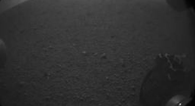 "This is the first image taken by NASA's Curiosity rover, which landed on Mars the evening of Aug. 5 PDT (morning of Aug. 6 EDT). It was taken through a ""fisheye"" wide-angle lens on one of the rover's rear left Hazard-Avoidance cameras."