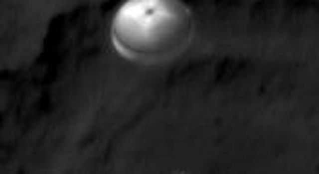 NASA's Curiosity rover and its parachute were spotted by NASA's Mars Reconnaissance Orbiter as Curiosity descended to the surface. The HiRISE camera captured this image of Curiosity while the orbiter was listening to transmissions from the rover.