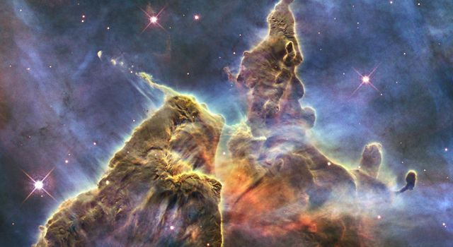 NASA's Hubble Space Telescope captures the chaotic activity atop a three-light-year-tall pillar of gas and dust that is being eaten away by the brilliant light from nearby bright stars in a tempestuous stellar nursery called the Carina Nebula.
