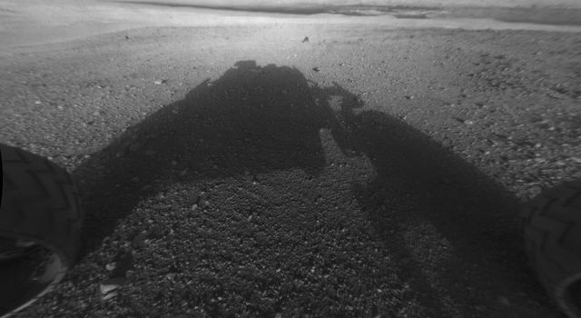 This image taken by NASA's Curiosity shows what lies ahead for the rover -- its main science target, informally called Mount Sharp. The rover's shadow can be seen in the foreground, and the dark bands beyond are dunes.