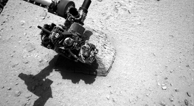 This image shows the robotic arm of NASA's Mars rover Curiosity with the first rock touched by an instrument on the arm. The rover placed the APXS instrument onto the rock to assess what chemical elements were present in the rock.