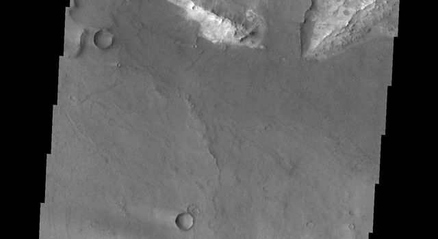 This image from NASA's 2001 Mars Odyssey spacecraft shows a portion of northeastern Syrtis Major. In this image are several windstreaks and a lava flow that has entered the crater on the top of the image.