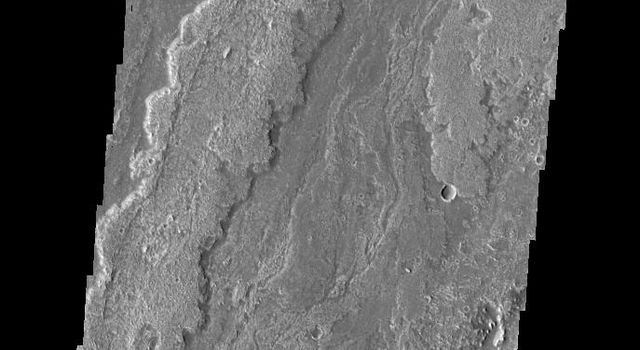 This image captured by NASA's 2001 Mars Odyssey spacecraft shows a small portion of Daedalia Planun, the result of vast eruptions of Arsia Mons.