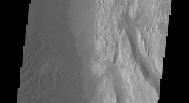 This image from NASA's Mars Odyssey spacecraft shows the western margin of Mt. Sharp. The large channel from past images enters the frame in the center and then veers to the northwest. A large region of sand and sand dunes covers the crater floor.