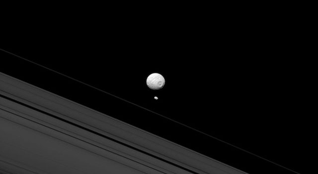 This image from NASA's Cassini spacecraft reminds us of how different Mimas and Pandora are when they appear together; although both are moons of Saturn, Pandora's small size means that it lacks sufficient gravity to pull itself into a round shape.