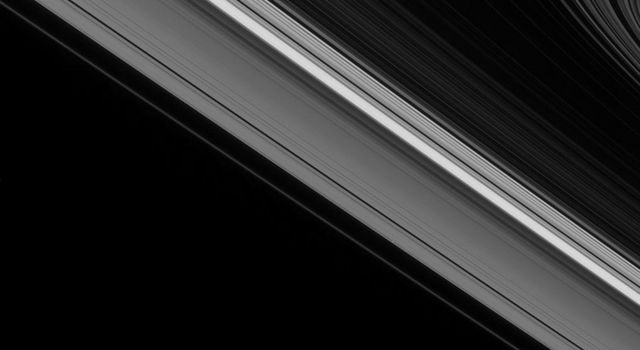 While the moon Epimetheus passes by, beyond the edge of Saturn's main rings, the tiny moon Daphnis carries on its orbit within the Keeler gap of the A ring in this image from NASA's Cassini spacecraft.