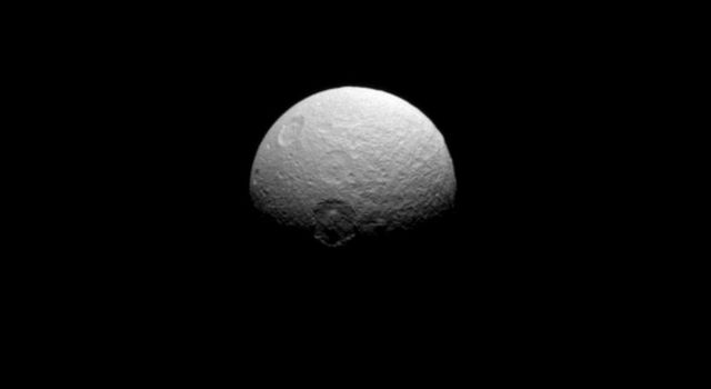 NASA's Cassini spacecraft captured this image of Tethys, telling the story of a violent history marked by impacts. Seen here are the craters Melanthius (near the center), Dolius (above Melanthius), and Penelope (upper left almost over the limb).