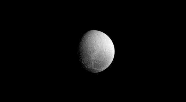 Although the crack-like features seen here on Dione's surface appear wispy and faded, they are in reality a series of geologically fresh fractures as seen in this images captured by NASA's Cassini spacecraft.