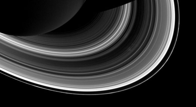 Among the interplay of Saturn's shadow and rings, Mimas, which appears in the lower-right corner of the image, orbits Saturn as a set of the ever-intriguing spokes appear in the B ring (to the right of center) in this image from NASA's Cassini spacecraft.