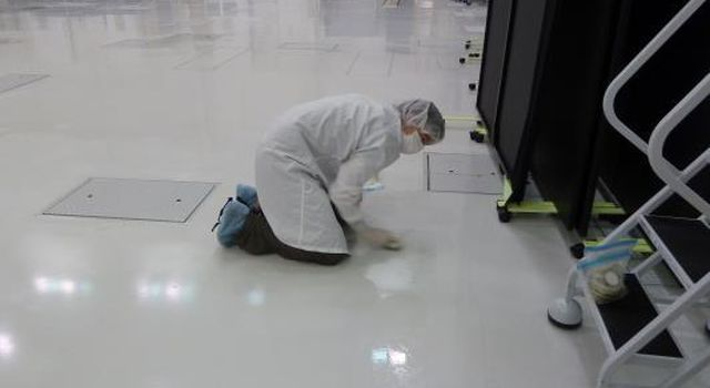 A microbiologist collects a swab sample from the floor of a spacecraft assembly clean room at NASA's Jet Propulsion Laboratory where samples such as this are taken frequently during the assembly of a spacecraft and analyzed.
