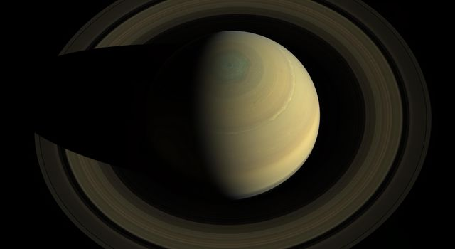 A swing high above Saturn by NASA's Cassini spacecraft revealed this stately view of the golden-hued planet and its main rings. Saturn sports differently colored bands of weather in this image.