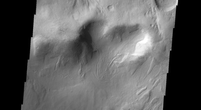 This image of Baltisk Crater shows a sand sheet on the crater floor and channels dissecting the outer rim as seen by NASA's 2001 Mars Odyssey spacecraft.