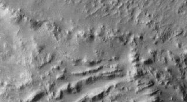 The landslide deposits in this infrared image from NASA's 2001 Mars Odyssey spacecraft are located in Valles Marineris and are called Coprates Labes.