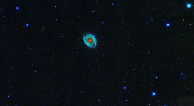 A dying star, called the Helix nebula, is shown surrounded by the tracks of asteroids in an image captured by NASA's WISE. Skirting around the edges of the Helix nebula are the footprints of asteroids marching across the field of view.