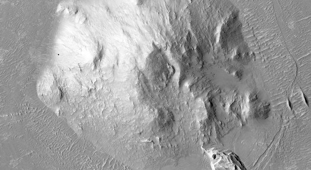 This image captured by NASA's Mars Reconnaissance Orbiter shows a central peak that is surrounded by a ring-like graben feature and relatively flat terrain.