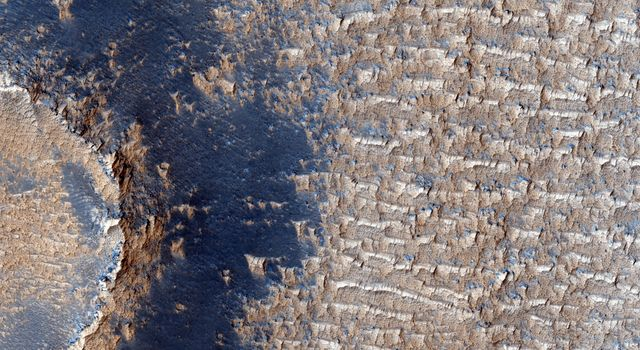 This image from NASA's Mars Reconnaissance Orbiter shows curious bright deposits in Syria Planum, a high elevation region near the summit of the Tharsis rise.