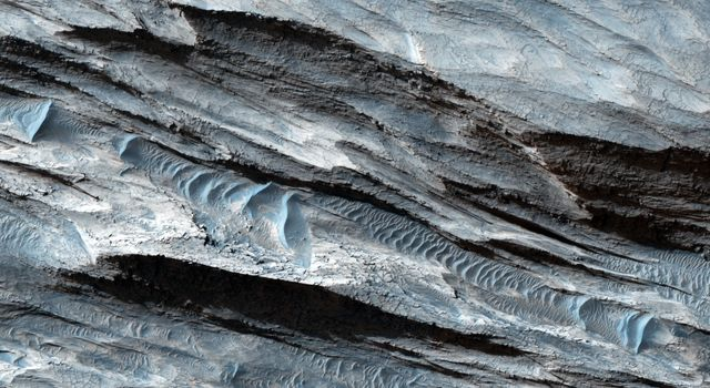 This basin in Ceti Mensa, as seen by NASA's Mars Reconnaissance Orbiter, exposes concentric rings in the sedimentary layers. Dark sand ripples and textures in the bedrock suggesting wind scouring are also apparent.