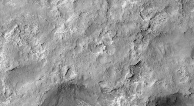 NASA's Curiosity Mars rover and tracks left by its driving appear in this portion of a Dec. 11, 2013, observation by the HiRISE camera on NASA's Mars Reconnaissance Orbiter. The rover is near the lower-left corner of this view.