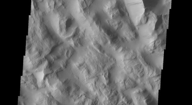 Dark slope streaks mark the hill sides in Lycus Sulci as seen by NASA's 2001 Mars Odyssey spacecraft.