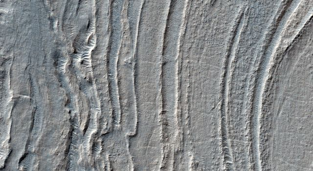 Low lying areas in the Hellas region, which is the largest impact basin on Mars, often show complex groups of banded ridges, furrows, and pits as seen in this observation from NASA's Mars Reconnaissance Orbiter.