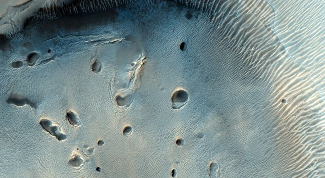 This fascinating observation from NASA's Mars Reconnaissance Orbiter shows us a dark-toned mound with pits inside an impact crater.