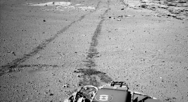 On Feb. 19, 2014, NASA's Curiosity Mars rover looked back after finishing a long drive. The rows of rocks just to the right of the fresh wheel tracks in this view are an outcrop called 'Junda.' This view is looking toward the east-northeast.